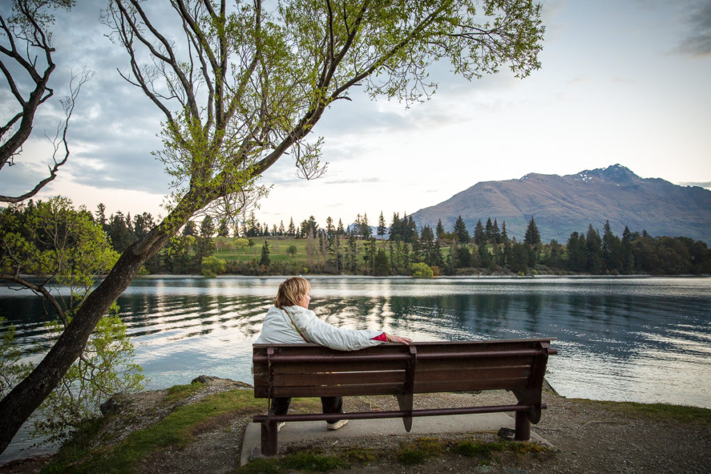 woman on park bench watches Queenstown view of lake